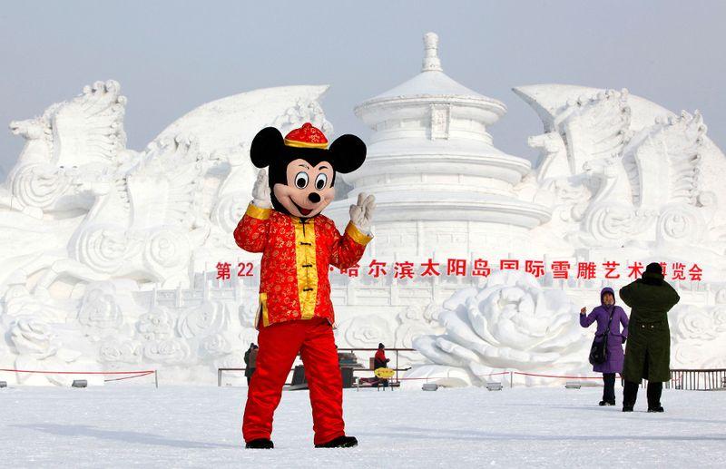 Человек в костюме Микки Мауса позирует перед скульптурой из снега в парке Харбина 5 января 2010 года. (REUTERS/Aly Song)