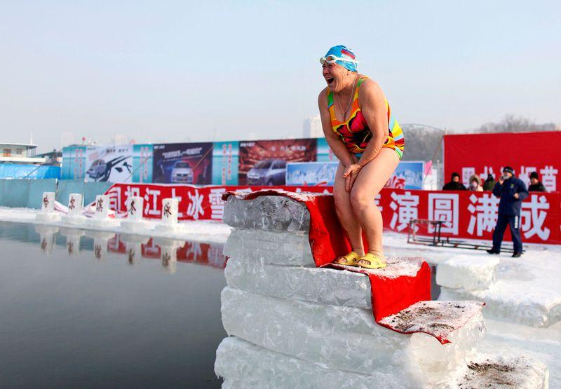 Женщина готовится прыгнуть в ледяную воду реки Сунхуа в Харбине 4 января 2010 года. (REUTERS/Aly Song)
