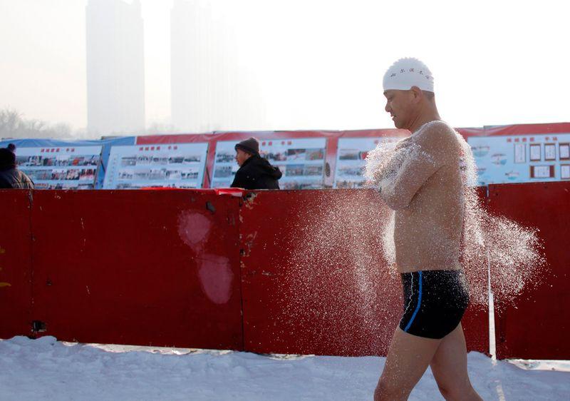«Морж» разогревается перед прыжком в холодные воды реки Сунхуа в Харбине 4 января 2010 года. (REUTERS/Aly Song)