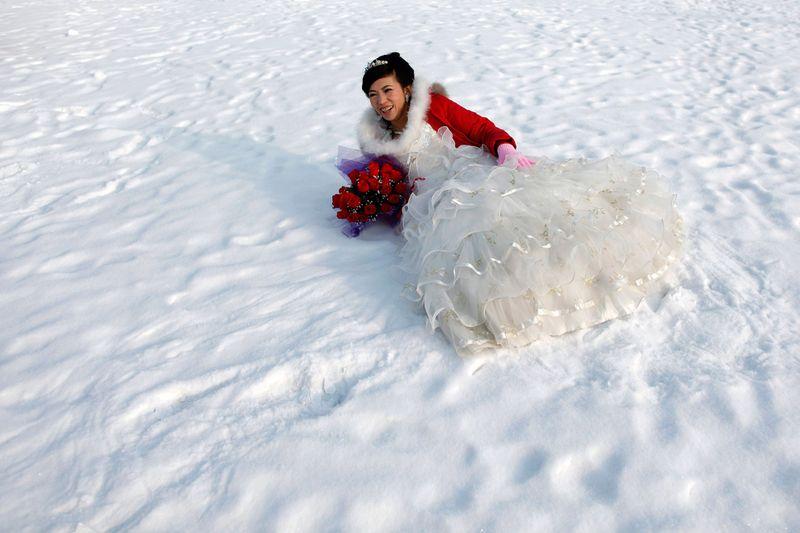Невеста позирует для фотографии после свадебной церемонии на 26-ом Международном фестивале снега и льда в Харбине, провинция Хэйлунцзян, Китай, 6 января 2010 года. (REUTERS/Aly Song)