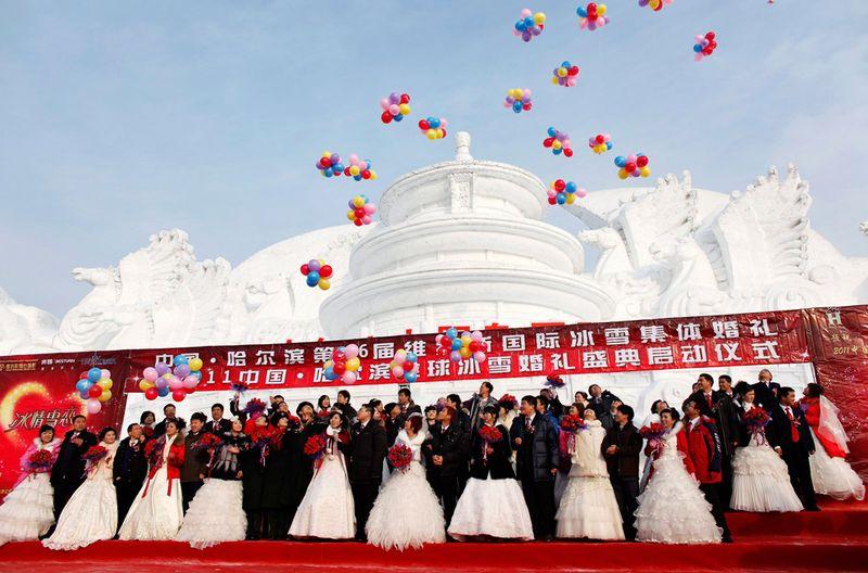 Пары принимают участие в групповой свадебной церемонии перед изображением Пекинского Храма Небес из снега 6 января 2010 года. Свадьба была организована правительством, и в церемонии приняли участие 28 пар, на которой присутствовали представители местных органов самоуправления. (REUTERS/Aly Song)