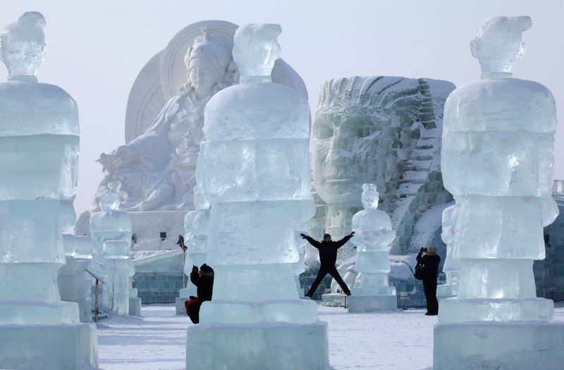 Посетители 26-ого Международного фестиваля снега и льда позируют рядом с гигантскими скульптурами в Харбине 5 января 2010 года. (AP Photo/Ng Han Guan)