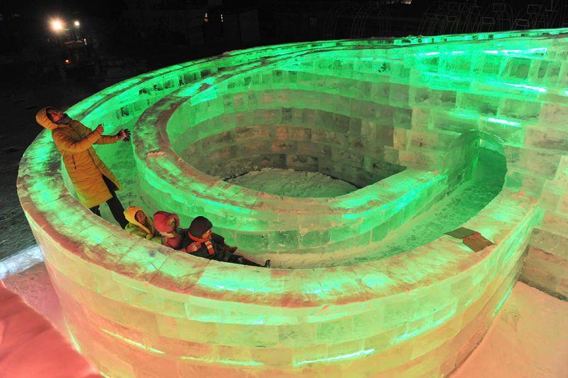 Посетители выставки играют в ледяной скульптуре до открытия фестиваля в Харбине 18 декабря 2009 года. (REUTERS/Sheng Li)