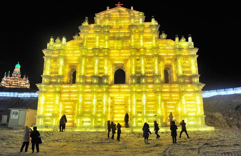 Люди пришли посмотреть на ярко освещенную изнутри ледяную скульптуру в Харбине 24 декабря 2009 года. (REUTERS/Sheng Li)