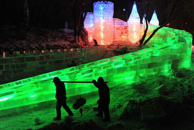 Рабочие проходят мимо ледяной скульптуры на фестивале в Харбине 18 декабря 2009 года. (REUTERS/Sheng Li)