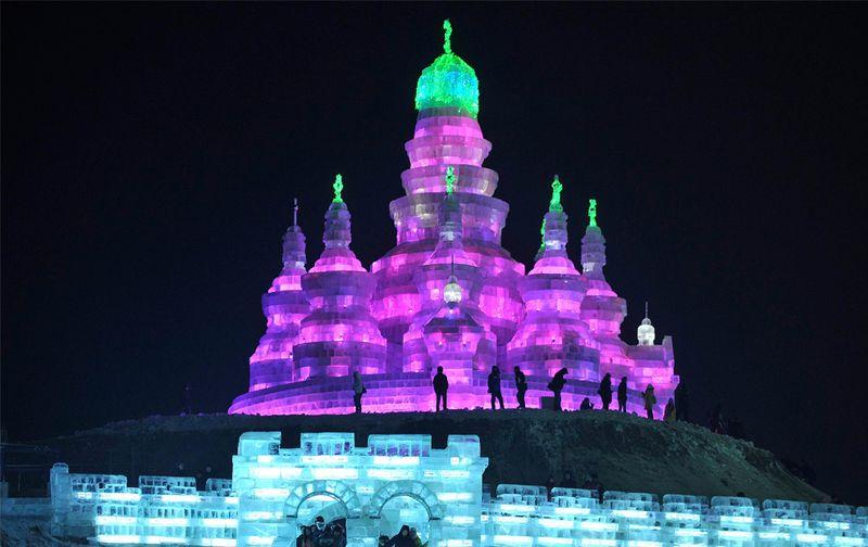 Люди пришли на ледяную скульптуру в парке Харбина 24 декабря 2009 года. (REUTERS/Sheng Li)