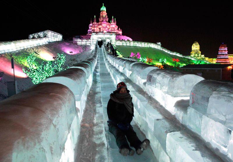 Женщина едет вниз с ледяной горки на фестивале в северо-восточной провинции Китая Хэйлунцзян 5 января 2010 года. (AP Photo/Ng Han Guan)