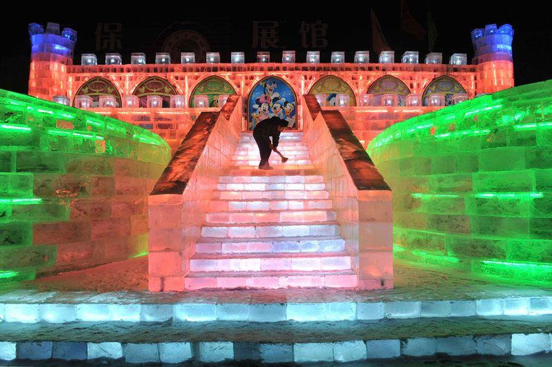 Рабочий чистит ледяную скульптуру в стиле Диснея перед открытием фестиваля снега и льда в Харбине 18 декабря 2009 года. (REUTERS/Sheng Li)