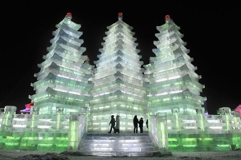 Люди пришли посмотреть на высокие ледяные пагоды в Харбине, провинция Хэйлунцзян, 24 декабря 2009 года. (REUTERS/Sheng Li)