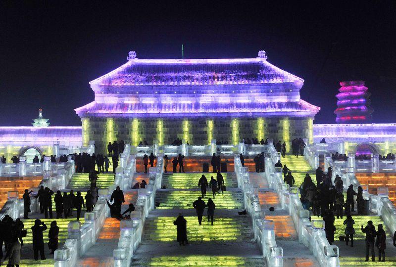 Люди идут по освещенным ступенькам на Международный фестиваль снега и льда 24 декабря 2009 года. (REUTERS/Sheng Li)