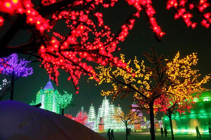 Освещенные яркими разноцветными гирляндами деревья и скульптуры в парке Харбина 6 января 2010 года. (AP Photo/Ng Han Guan)