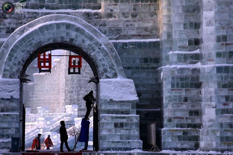 Рабочие завершают работу над скульптурой изо льда у входа на фестиваль снега и льда в Харбине 4 января. (REUTERS/David Gray)