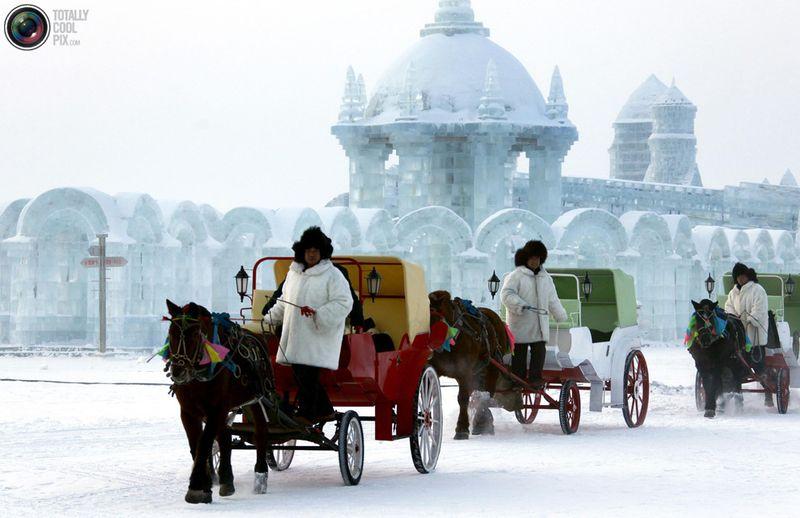 Кареты с лошадьми на фоне ледяных скульптур на фестивале в Харбине. (REUTERS/David Gray)
