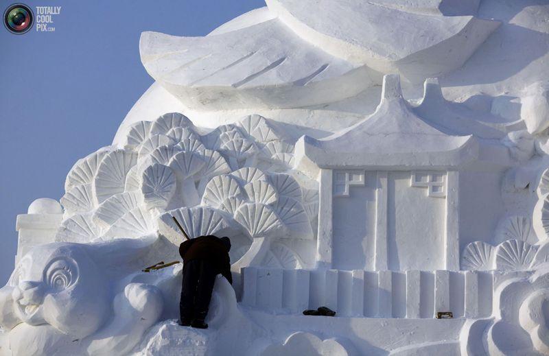 Рабочий заканчивает скульптуру из снега. (REUTERS/David Gray)