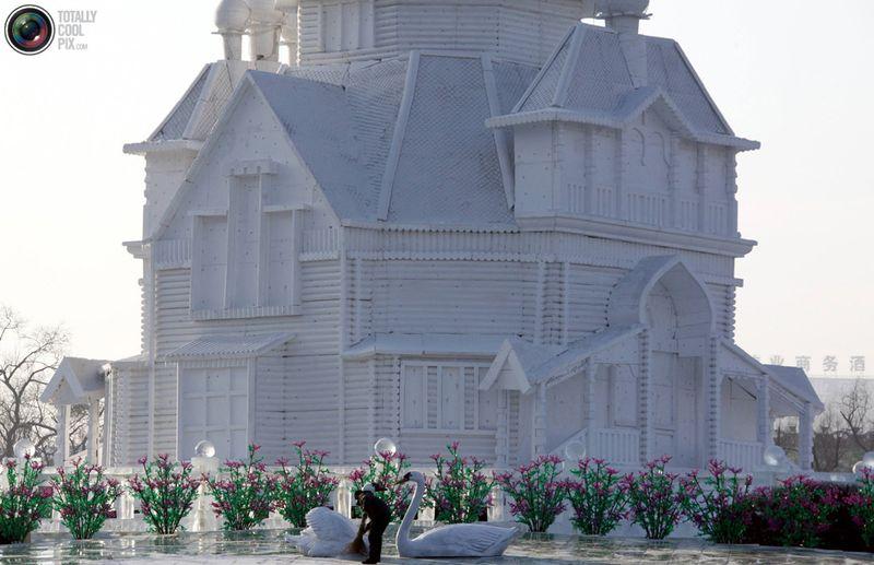 Рабочий подметает у огромной скульптуры дома из снега на перекрестке в Харбине. (REUTERS/David Gray)