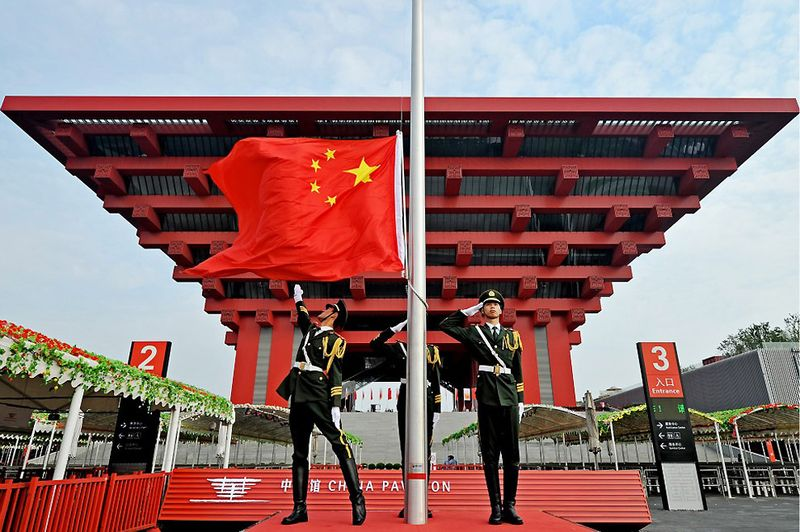 6. 1 октября 2010 года в день основания Китайской Народной Республики перед Китайским павильоном на выставке ЭКСПО-2010 солдаты подняли флаг КНР. (PHILIPPE LOPEZ/AFP/Getty Images)