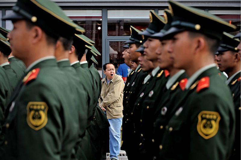 8. Уставший зритель смотрит на ряды солдат Народно-освободительной армии Китая в первый день выставки ЭКСПО-2010, 1 мая. За полгода работы выставки ее посетило рекордное количество человек, составившее 73 миллиона. Самая большая посещаемость была зарегистрирована 16 октября 2010 – 1,03 миллиона посетителей за день. (PHILIPPE LOPEZ/AFP/Getty Images)
