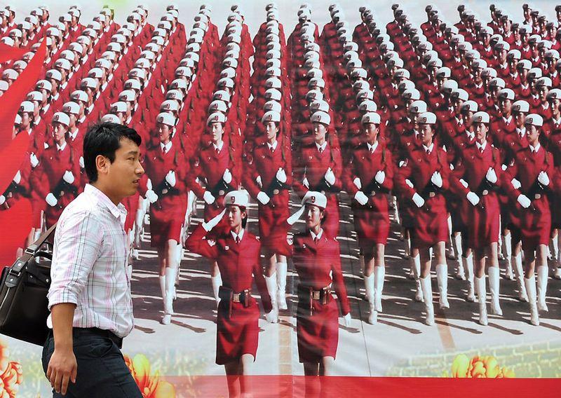 10. Прохожий на фоне рекламного щита с фотографией парада Народно-освободительной армии Китая в честь 60-й годовщины правления Коммунистической партии, отмечавшейся в 2009 году. (FREDERIC J. BROWN/AFP/Getty Images)