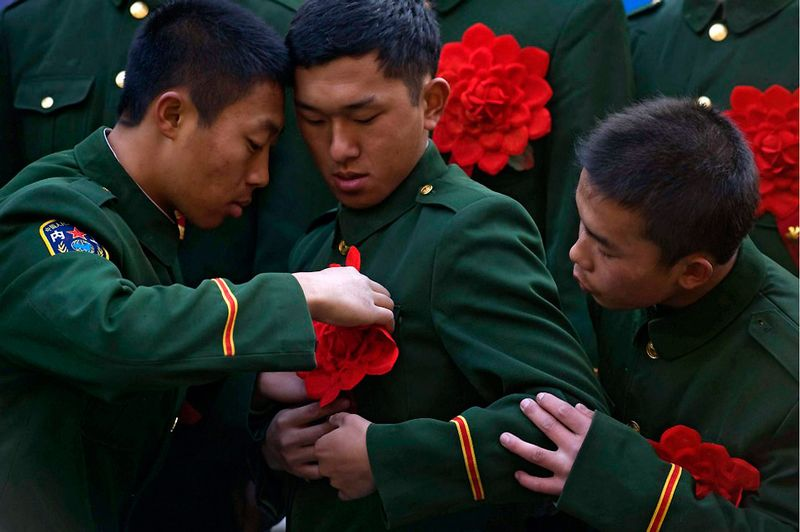 20. За порядком на площади Тяньаньмэнь следят члены Народной вооружённой милиции Китая. Перед церемонией смены караула к мундирам прикрепляются специальные украшения. 3 ноября 2009. (STR/AFP/Getty Images)