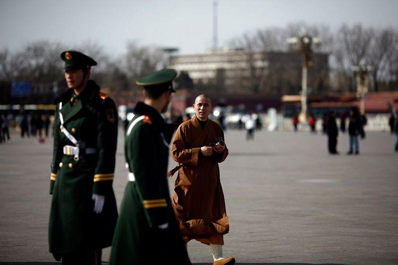 27. Монах идет мимо наряда полиции на площади Тяньаньмэнь 2 марта. Перед проведением ежегодной сессии китайского парламента в Доме народных собраний охрану площади всегда усиливают. (Li Xin/AFP/Getty Images)