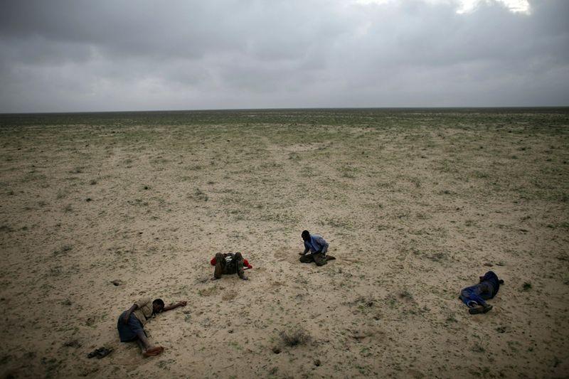 1. Четыре сомалийских беженца по дороге в Йемен спят в пустыне после ночного путешествия по грязным дорогам под дождем 15 марта. Фотография заняла первое место в категории «Проблемы современности». (Reportage by Getty Images.)