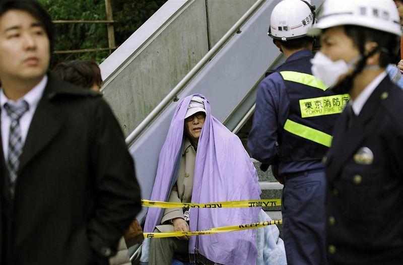 Мужчина под одеялом после эвакуации из здания в финансовом районе Токио. (Kim Kyung-hoon / Reuters)