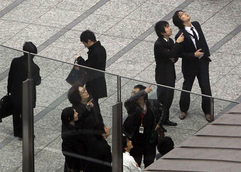 Офисные рабочие в районе Сиодомэ, недалеко от Токийского залива, оценивают ущерб, нанесенный землетрясением зданиям офисов и отелям. (Koji Sasahara / AP)