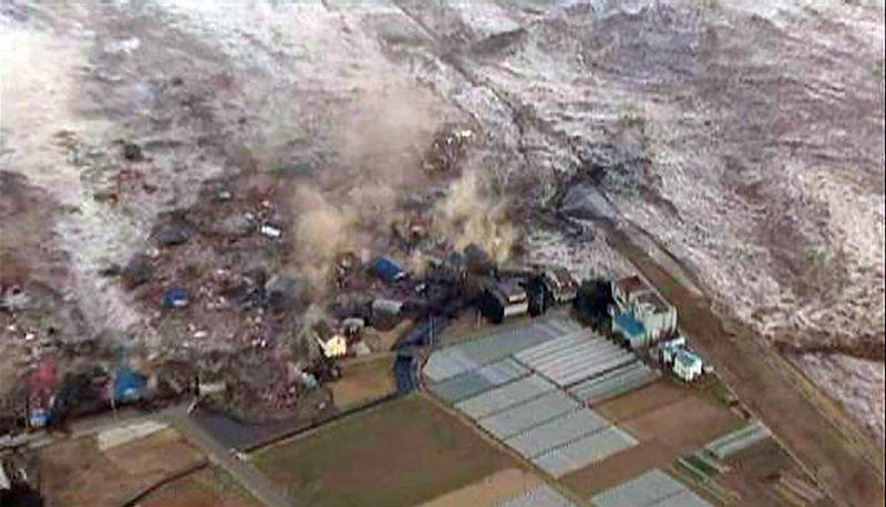 Цунами сносит здания в портовом городе Камаиши. (Str / Reuters)