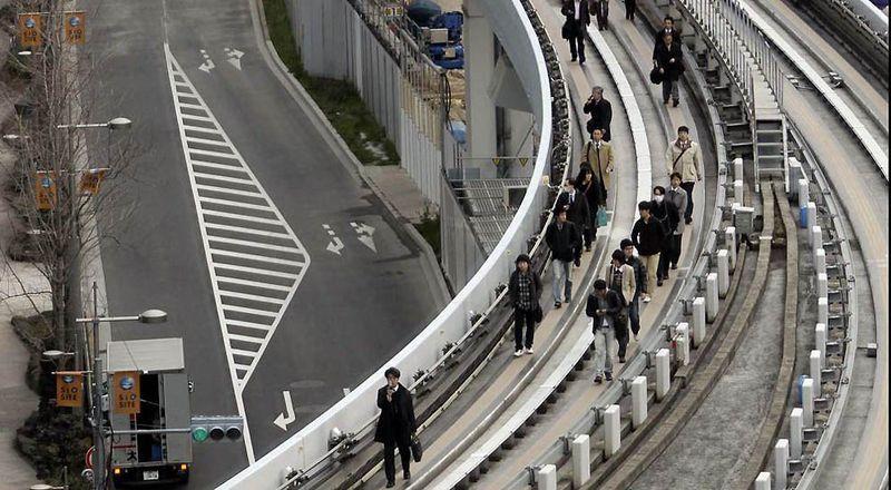 Пассажиры поезда Юрикамоме идут по поднявшимся рельсам на станции Сиодомэ, недалеко от Токийского залива. (Koji Sasahara / AP)