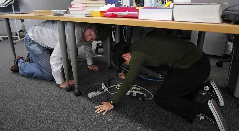 Прячущиеся под столом репортеры агентства «Associated Press» во время землетрясения в Токио. (Itsuo Inouye / AP)