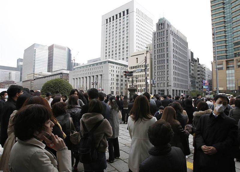 Люди вышли на улицу во время эвакуации после землетрясения в финансовом районе Токио. (Toru Hanai / Reuters)