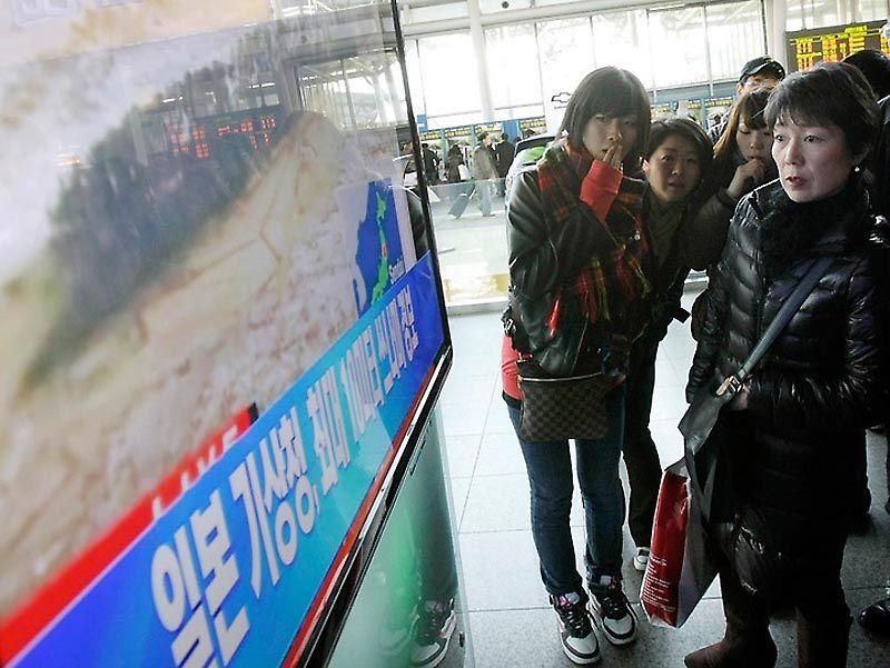"""Японские туристы смотрят телевизионную программу новостей о сильном землетрясении в Японии. Снимок сделан в знании железнодорожного вокзала в Сеуле, Южная Корея. Надпись внизу экрана: """"Японское метеорологическое агентство предупреждает о цунами"""". (AP Photo/Ahn Young-joon)"""