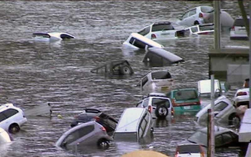 На этом кадре из видео телеканала NHK видны смытые цунами автомобили у восточного побережья Японии. (AP Photo/NHK TV)
