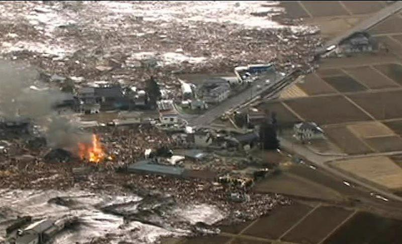 Кадр из видео японского телеканала NHK, на котором видны дома, разрушенные цунами в городе Сендай на востоке Японии. (AP Photo/NHK TV)