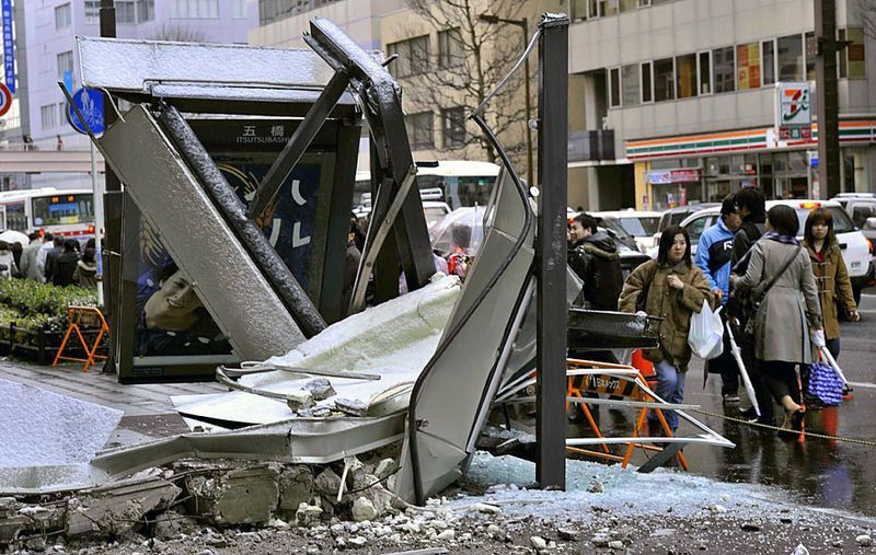 Люди идут мимо рухнувшей автобусной остановки в городе Сендай. (Kyodo News/AP)