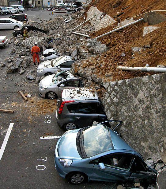 Автомобили под рухнувшей стеной в городе Сендай. (JIJI PRESS / AFP/Getty Images)