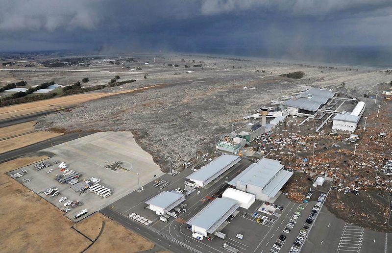 Вызванное землетрясением цунами несется к аэропорту Сендай в северной Японии 11 марта. (Kyodo News/Associated Press)