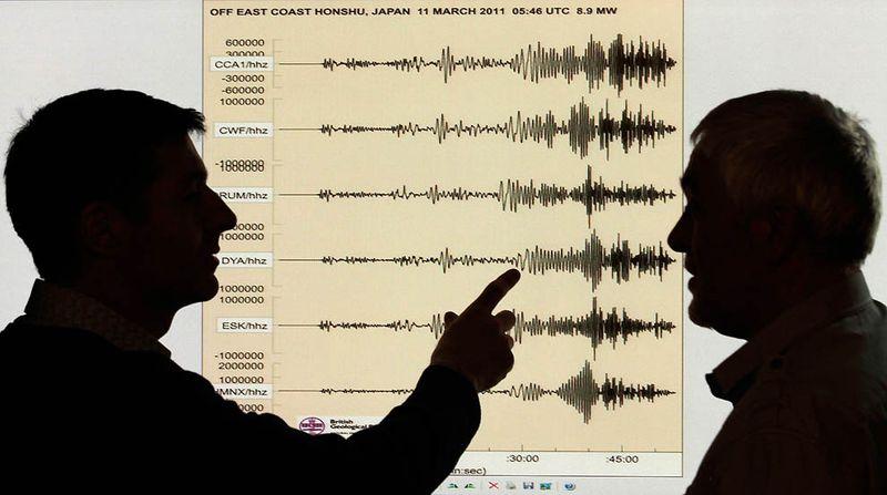 Сейсмологи на фоне диаграммы, демонстрирующую мощность землетрясения в Японии. Снимок сделан в офисе британской геологической службы в Эдинбурге. 11 марта в пятницу на Японию обрушилось крупнейшее землетрясение в истории страны. (David Moir/Reuters)