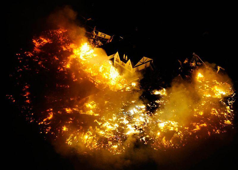 Охваченный огнем дом недалеко от аэропорта Сендай после мощного землетрясения. (Kyodo News/Associated Press)