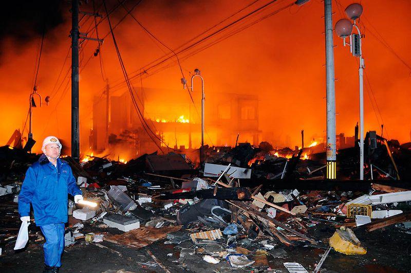 Спасатель среди обломков и горящих зданий после сильнейшего в истории Японии землетрясения. (Kyodo News/Associated Press)