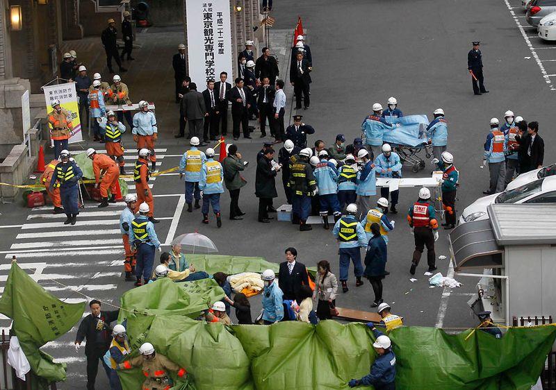 Спасатели спешат к зданию после сообщений о жертвах в финансовом районе Токио. После землетрясения было несколько ощутимых афтершоков и мощное цунами, обрушившееся на прибрежные города страны. (Kim Kyung-Hoon/Reuters)