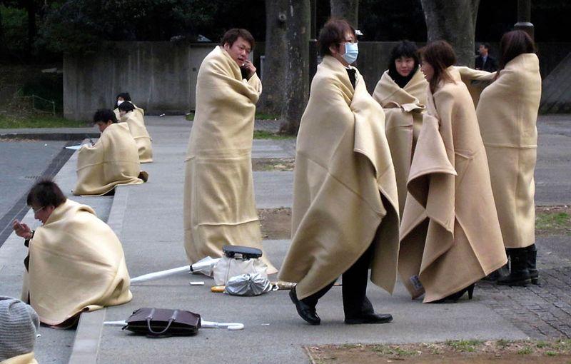 Укрывающиеся в одеяла прохожие в парке в Йокохаме после сильного землетрясения. (Shuji Kajiyama/Associated Press)
