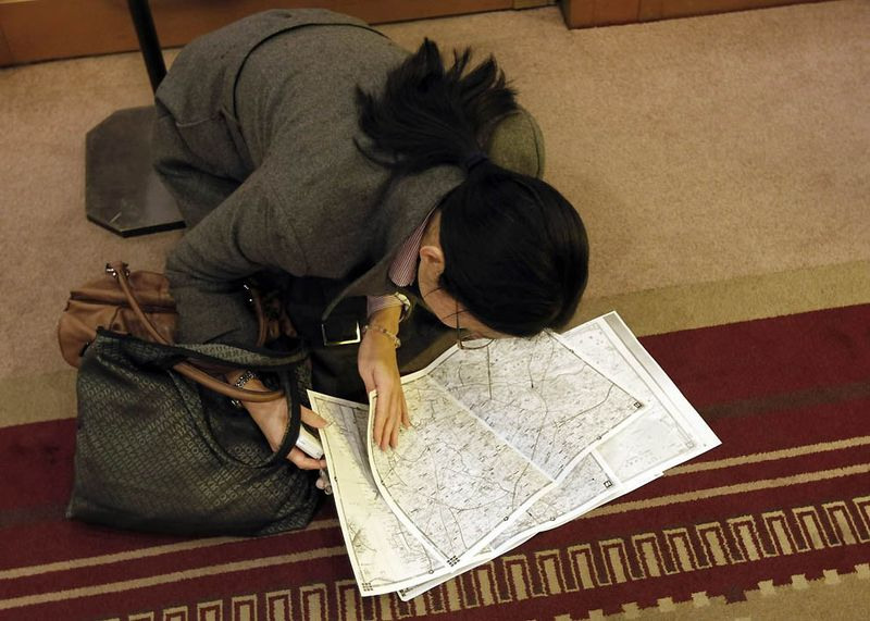 Сверяющая карты девушка пытается найти маршрут в вестибюле отеля, после того как в Токио приостановили движение метро и поездов. (Kim Kyung-Hoon/Reuters)