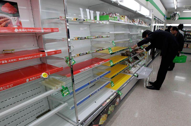 Покупатель ищет продукты почти пустых полках одного из токийских магазинов, после того как люди раскупили все, так как не могут вернуться домой после землетрясения. (Yuriko Nakao/Reuters)