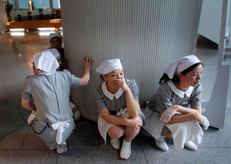 Работницы отеля в ужасе сидят у входа в отель в Токио. (Itsuo Inouye/Associated Press)