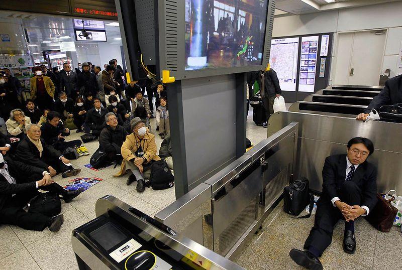 Оставшиеся без транспорта жители сморят новости после землетрясения на ж/д станции в Токио. (Hiro Komae/Associated Press)