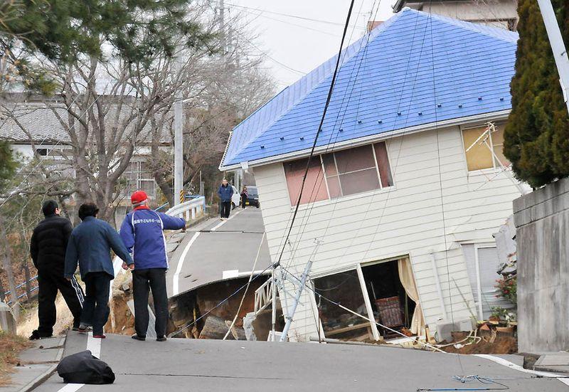 Жители оценивают ущерб на дороге в Сукагаве, префектура Фукусима. (Fukushima Minpo/AFP/Getty Images)