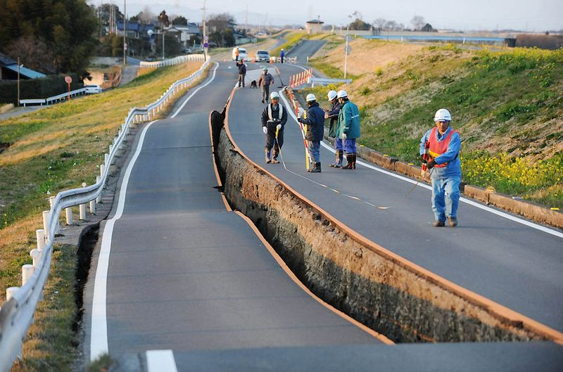 Рабочие осматривают обвалившийся участок дороги в Сатте, префектура Саитама, после землетрясения. (Saitama Shimbun/Associated Press/Kyodo News)