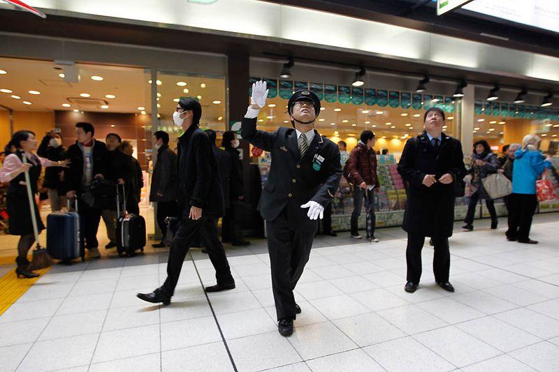 Работник станции Синагава руководит движением пассажиров после землетрясения в Токио. (Hiro Komae/Associated Press)