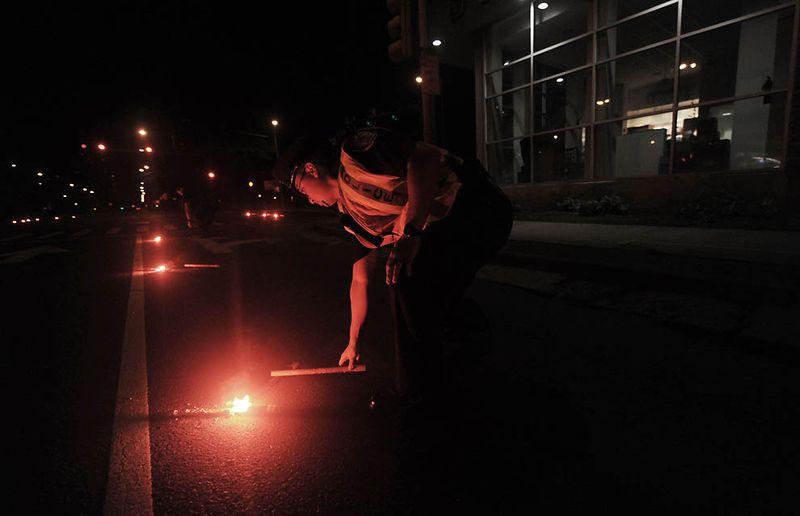 Полицейские кладут на дорогу факелы в Гонолулу. После того, как землетрясение силой в 8,9 баллов обрушилось на побережье Японии, вызвав цунами, тысячи людей на Гавайях были эвакуированы из своих домов. (Lucy Pemoni/Getty Images)